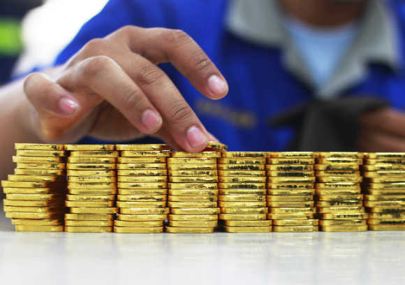 An employee holds a gold piece, each weighing 100 grams, at the state-owned mining company PT Antam Tbk metal refinery in Jakarta, Indonesia.