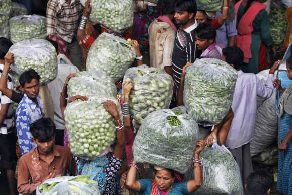 People carry vegetable bags at a wholesale market in Ahmedabad.