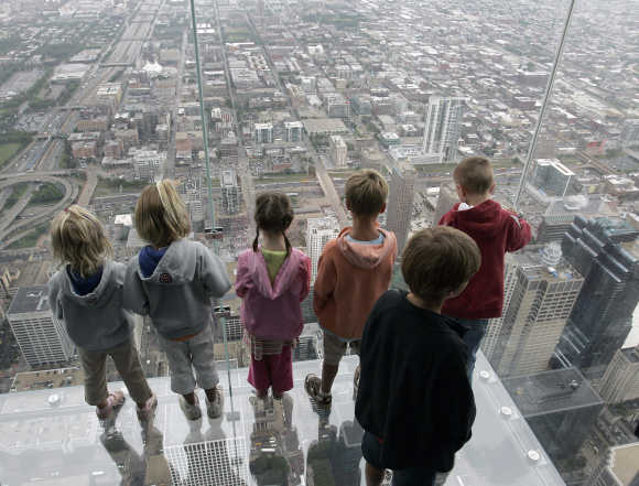 It is sometimes tough being Indian and trying to start a business, says Nemani. Children stand on 'The Ledge', a five-sided glass box 1,353 feet above the street in Chicago. The Ledge is part of Skydeck Chicago located on the 103rd floor of the Sears Tower.