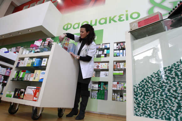 A pharmacist arranges drugs inside a pharmacy in Athens.