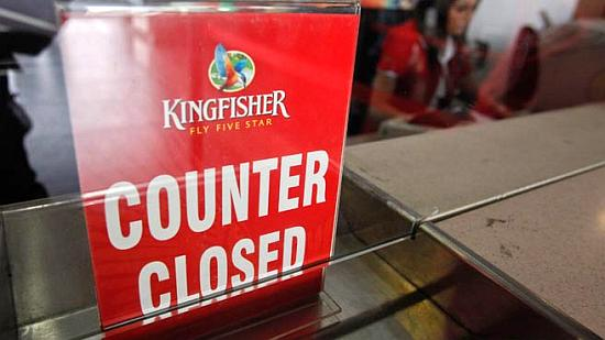 An employee of Kingfisher Airlines works next to a ''counter closed'' sign before the airline stopped operations.