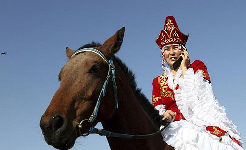 A woman speak on a mobile phone while attending an equestrian games festival in Bishkek.