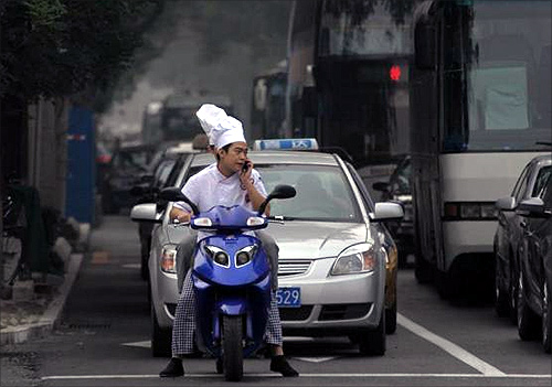 A motorist talks on his mobile phone as he waits at traffic lights in Beijing.