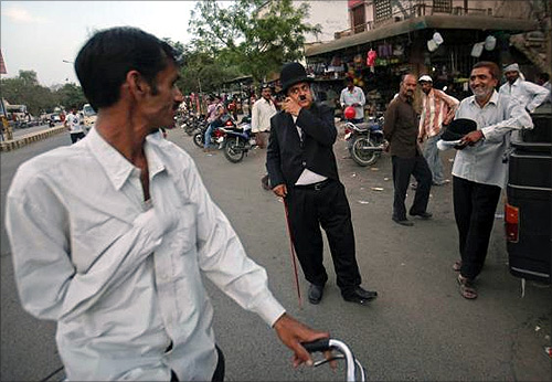 Ashok Aswani, a 63-year-old doctor dressed up as Charlie Chaplin, talks on a phone along a road in Adipur, Gujarat.