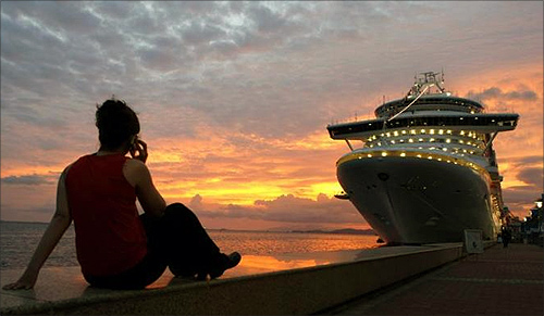 A woman talks on her phone while watching the sun set behind a cruise ship used to house attendees to the Summit of the Americas in Port of Spain, Trinidad.