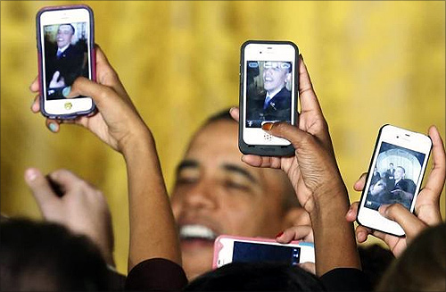 Attendees photograph President Barack Obama with their mobile phones at a Women's History Month reception at the White House in Washington.