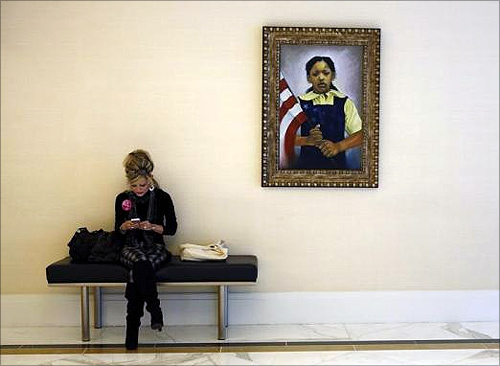 A woman uses her mobile phone as she sits under a portrait of a young girl while attending the Conservative Political Action Conference (CPAC) at National Harbor, Maryland.