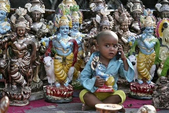 Prem (3), the son of an idol vendor, plays with a mobile phone in front of the idols of Hindu god Krishna.