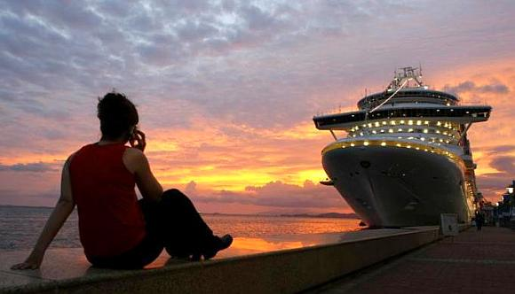 A woman talks on her phone while watching the sun set behind a cruise ship.