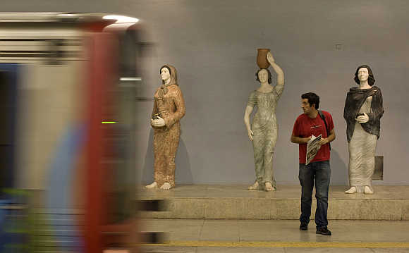 A subway passenger watches the arrival of a train in front of marble statues of traditional figures in Lisbon, Portugal.