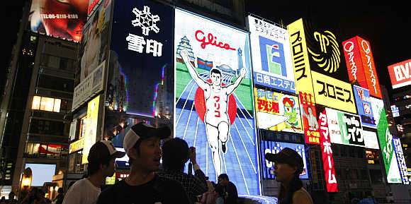 Passers-by are silhouetted against advertisements in the Dotonbori shopping and amusement district in Osaka, western Japan.