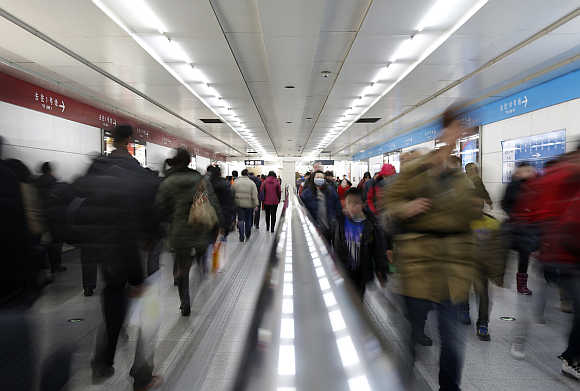 Passengers walk inside a subway station in Beijing, China.