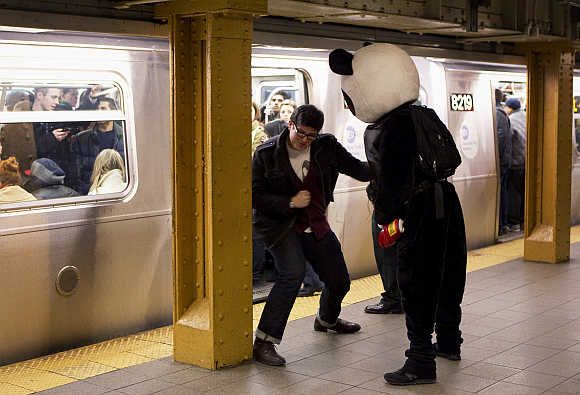 A man punches another man dressed up as 'Punch Me Panda' inside the subway system in New York City.