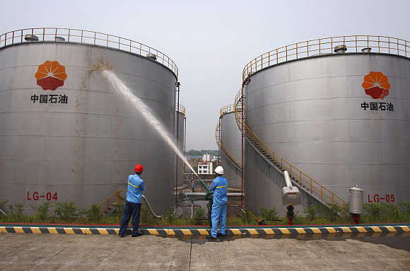 Employees spray water to cool down oil tanks at a storage facility belonging to PetroChina oil, in Suijing, Sichuan Province, China.