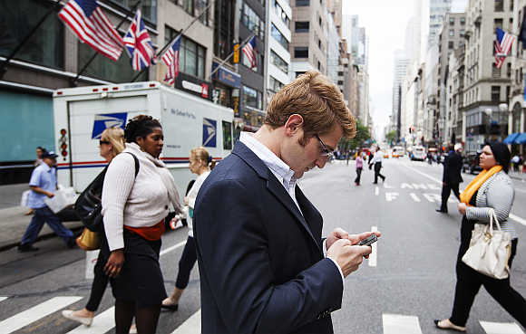 A man uses mobile phone while walking across 5th Avenue in New York.