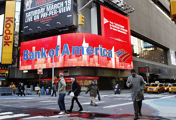 Pedestrians walk past a Bank of America sign on a building in Times Square in New York.