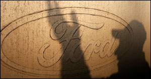 The shadow of a worker is seen on the logo of Ford Motor Co