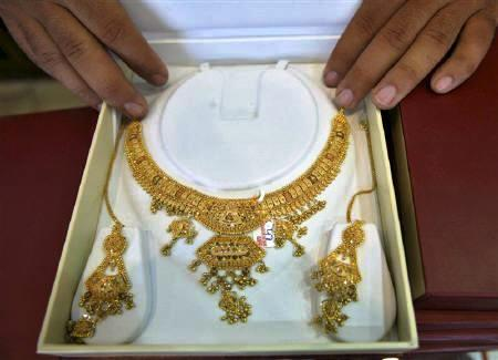 A shopkeeper displays gold jewellery inside his showroom.