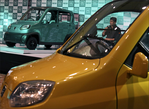 Bajaj's Managing Director Rajiv Bajaj is seen through the windows of the newly launched first-ever four-wheeled vehicle RE60 in New Delhi.