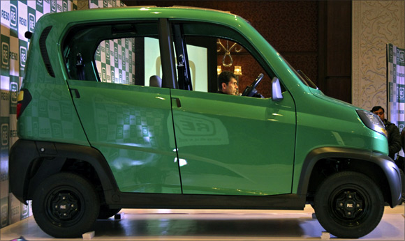 Bajaj's Managing Director Rajiv Bajaj is seen through the windows of the newly launched first-ever four-wheeled vehicle RE60.
