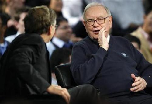Investor Warren Buffett (R) whispers to Microsoft Corporation founder Bill Gates (L).