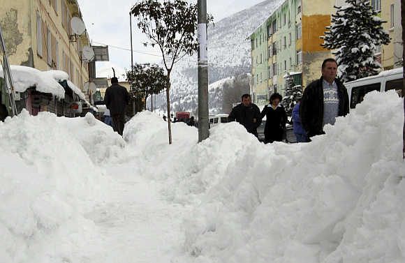 People walk after snowfall in the city of Bulqize, some 140km north of capital Tirana in Albania.