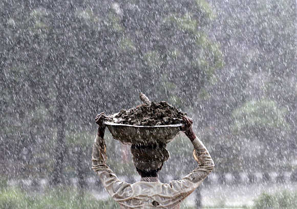 A labourer carries a container of mud as it rains in Noida.