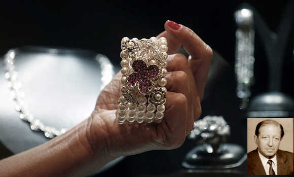 A shop assistant shows a bracelet from Brazilian designer Mauricio Monteiro, containing a selection of large pink sapphires, pearls and diamonds, at the Iguatemi mall in Sao Paulo, Brazil. Inset, Robert Fayez Mouawad.