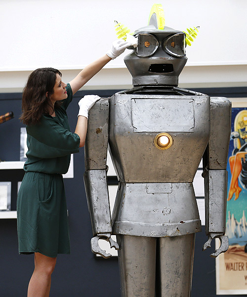A Christie's employee poses with Cygan, a giant robot made by Italian engineer Piero Fiorito in 1957, at Christie's in London.