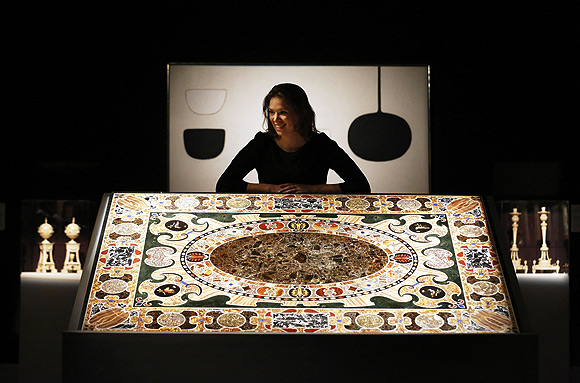 A Sotheby's employee poses with William Scott's Permutation 3 - White (top) and a Late Renaissance Antique Marble Inlaid Table Top at Sotheby's Auction House in London.
