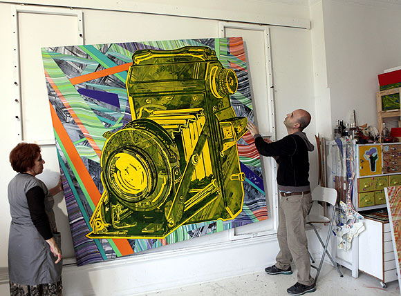 Turkish artist Yigit Yazici (R) fixes one of his artworks at his studio in Istanbul.