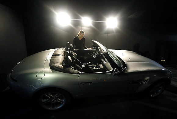 A worker poses next to a pre-production replica BMW Z8 Roadster made for the film The World is not Enough, during a media preview of 50 Years of James Bond - the Auction, at Christie's in London September.
