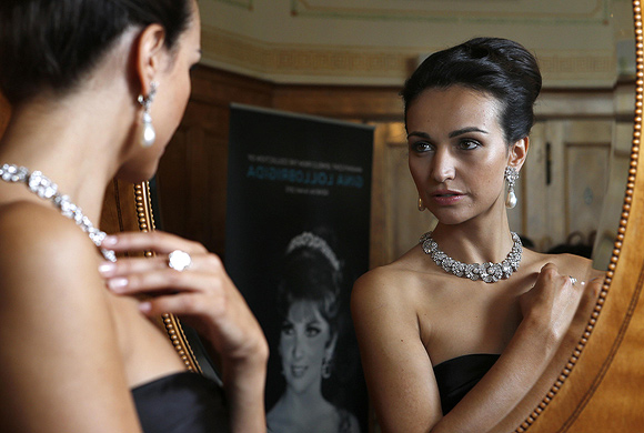 A model wears a diamond necklace/bracelet by Bulgari (1954) a natural pearl and diamond pendant earrings(1962) and a diamond ring (1962) during an auction preview at Sotheby's in Geneva.