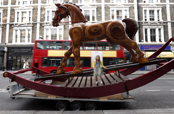 Riva Lemanski, 6 poses on a giant two-storey rocking horse outside Christie's auction house in London.