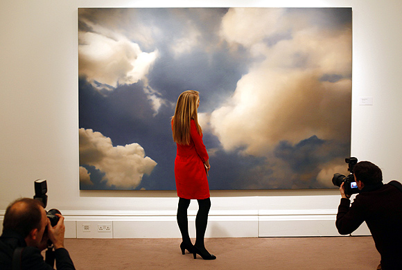 A Sotheby's worker poses next to Wolke (Cloud) from 1976 by Gerhard Richter, at Sotheby's in London.