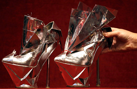 An assistant displays Platform shoes owned by singer Lady Gaga at the Hotel Drouot auction house in Paris.