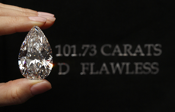 A Christie's member of staff displays a pear-shaped, D colour, flawless diamond of 101.73 carats during an auction preview in Geneva.