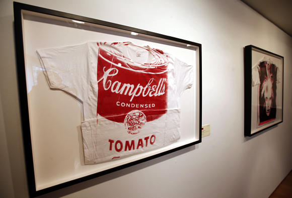 Artist Andy Warhol's 'Campbell's Tomato Soup' (L), a screen print on t-shirt, ca 1981 (estimate is $12,000 to 15,000) and 'Self-Portrait with Fright Wig' (R), a screen print on t-shirt, ca. 1986 (estimate is $15,000-20,000)  are seen on display at Christie's in New York City.