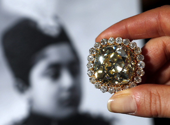 A Sotheby's staff member holds a fancy yellow 74.53 carat diamond and diamond jewel from the late 19th century during an auction preview in Geneva.
