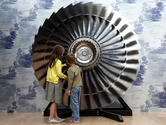 Riva Lemanski 6, and her brother Elia 4, turn a Stage 1 Rolls Royce RB Titanium Turbine Fan from 1970 at Christie's in London.
