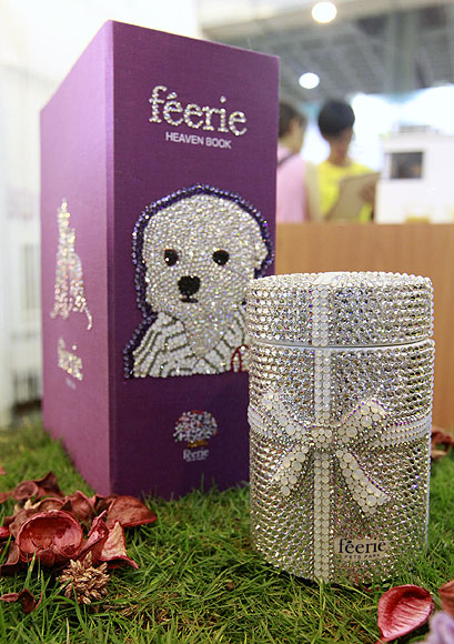 A pet urn (R) decorated with crystal and a book-shaped casket are seen at the 2013 Taipei Pet Show at Nangang Exhibition Hall in Taipei.