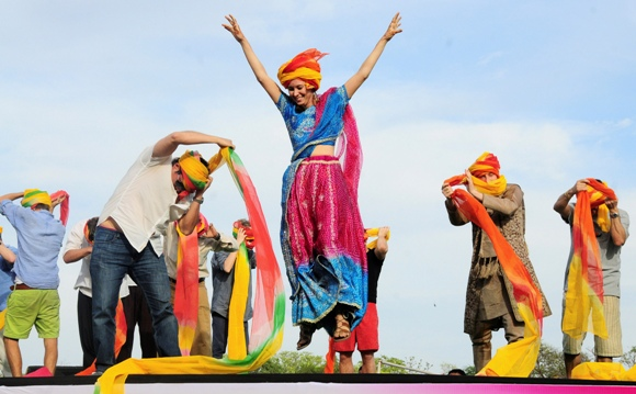 A tourist celebrates after finishing first in a turban tying competition held as part of the celebrations of Holi in Jaipur.
