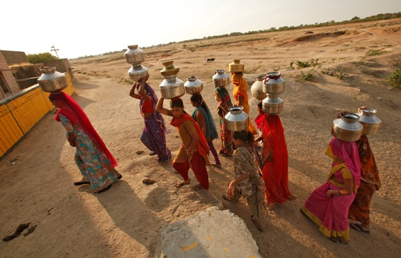 Women carry metal pitchers containing drinking water to their homes at Merta district in Rajasthan.