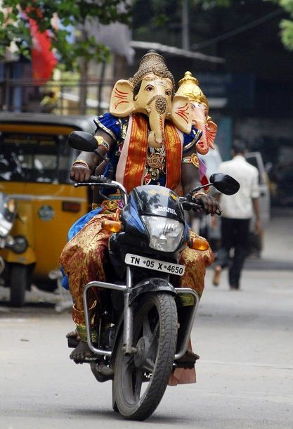 A man wearing an elephant mask on a bike in Chennai.