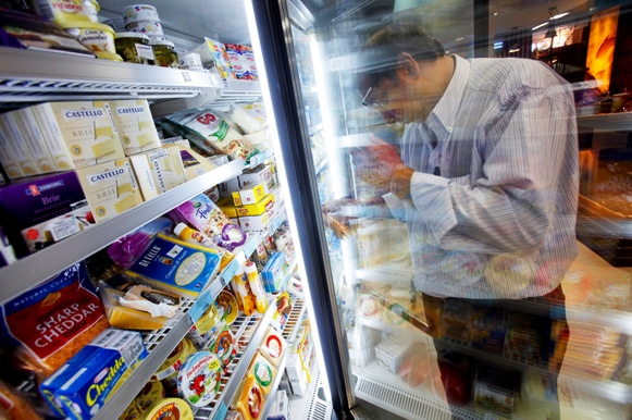 A customer examines a packet of cheese in the processed dairy food section of a supermarket in Mumbai.