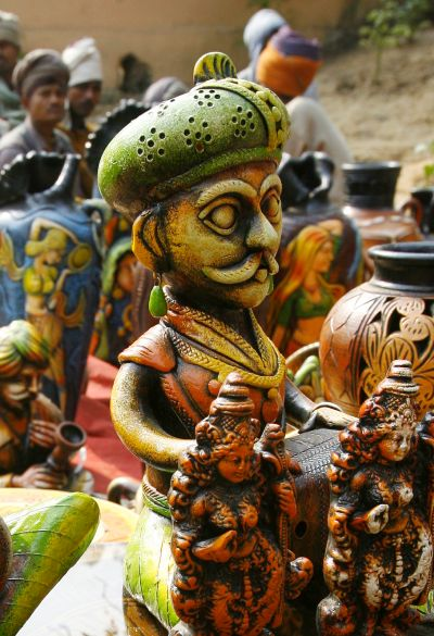 Labourers sit near a stall of sculptures at the Surajkund Crafts Fair in the northern Indian state of Haryana.