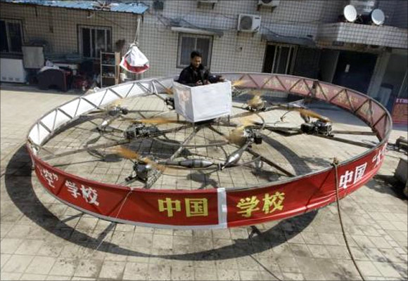Local farmer Shu Mansheng hovers above the ground in his self-designed and homemade flying device during a test flight in front of his house in Dashu village on the outskirts of Wuhan, Hubei province.