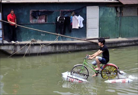 Lei Zhiqian rides a modified bicycle across the Hanjiang River, a tributary of the Yangtze River in Wuhan, Hubei province, China.