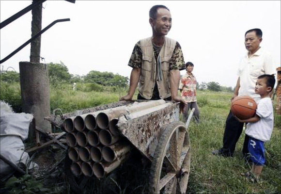 Chinese farmer Yang Youde pushes his homemade cannon near his farmland on the outskirts of Wuhan, Hubei province, China.
