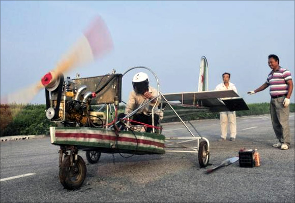 Ding Shilu (L) tests the engine of his home-made aircraft before conducting a test flight on the outskirts of Shenyang, Liaoning province.